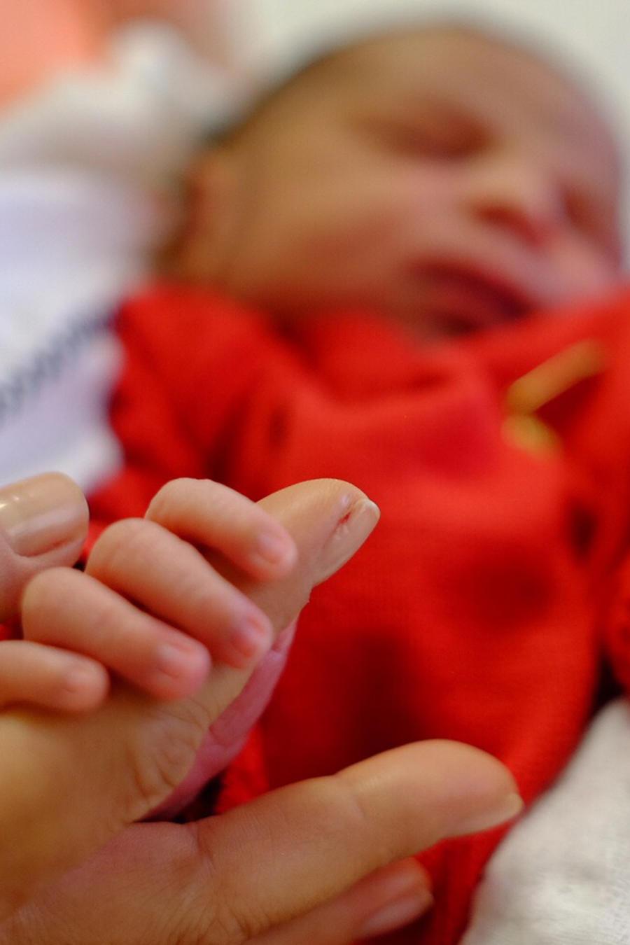 Mamá sosteniendo la mano de su bebé recién nacido