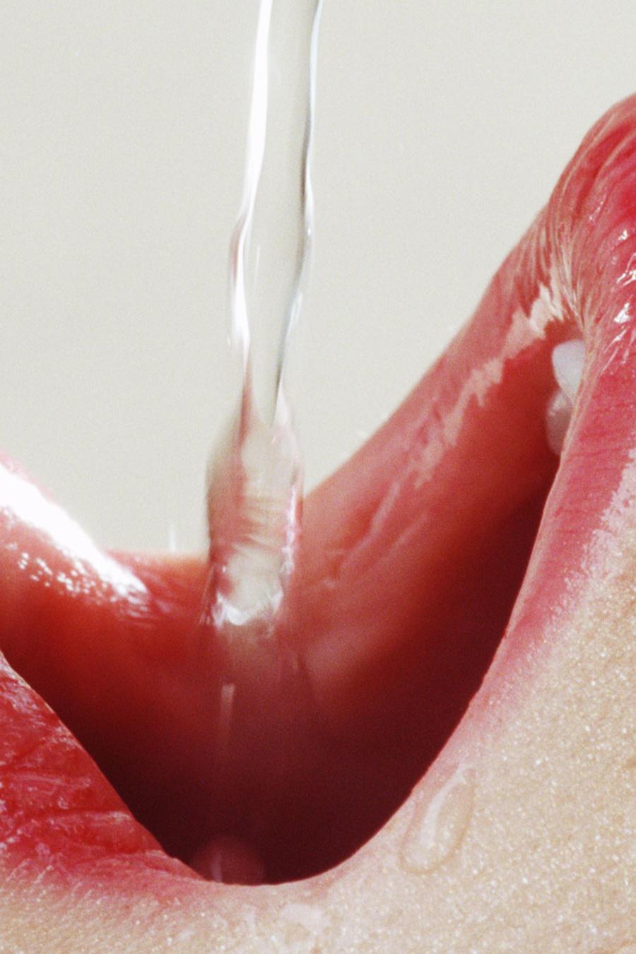 Agua cayendo sobre la boca de una mujer