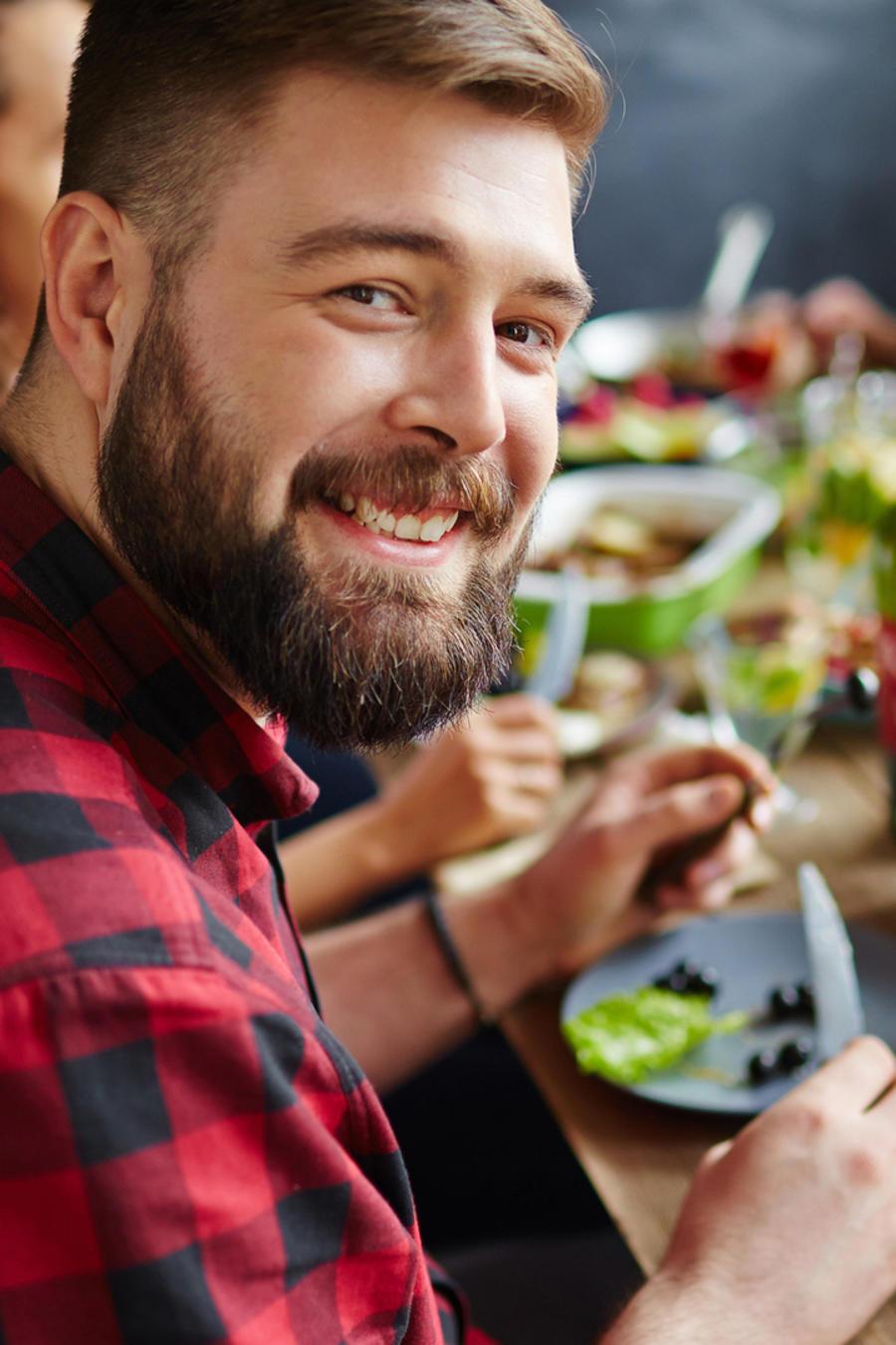 Hombre joven comiendo con amigos