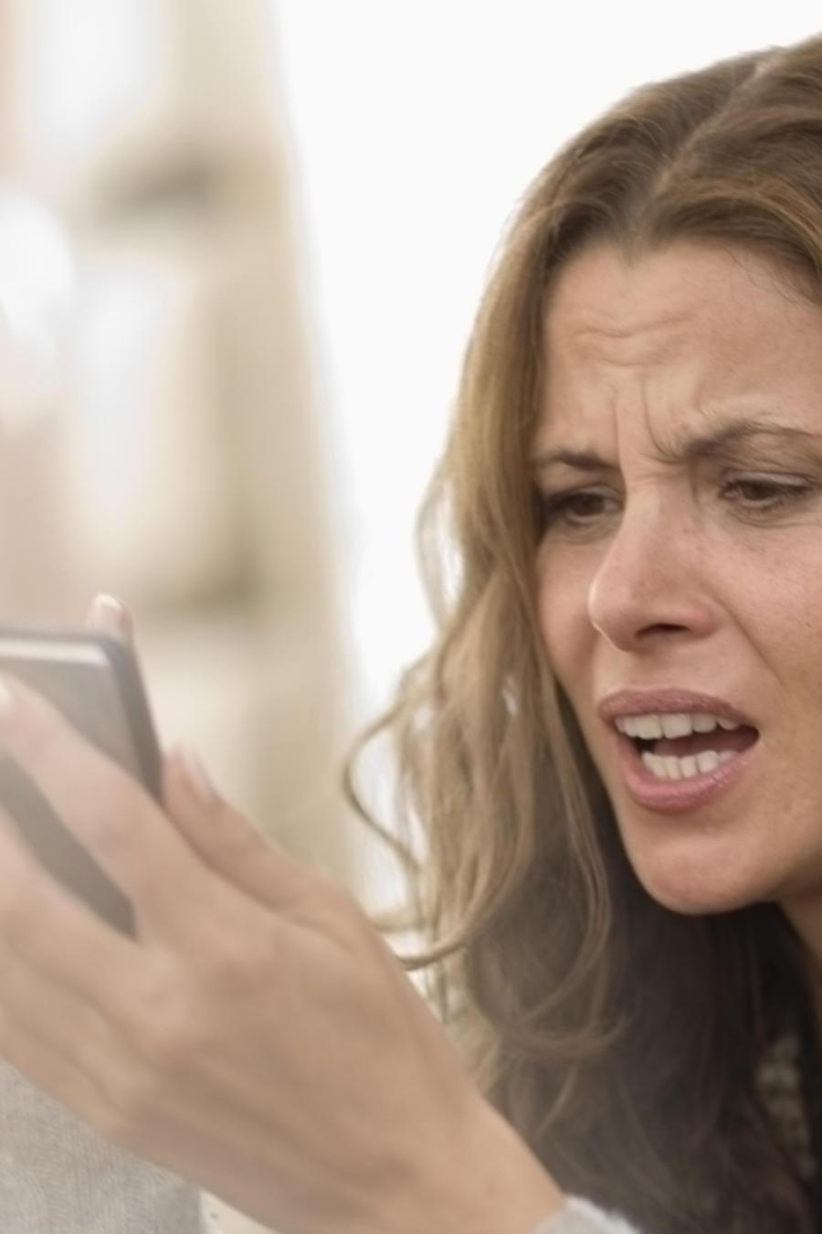 Mujer leyendo un mensaje enojada
