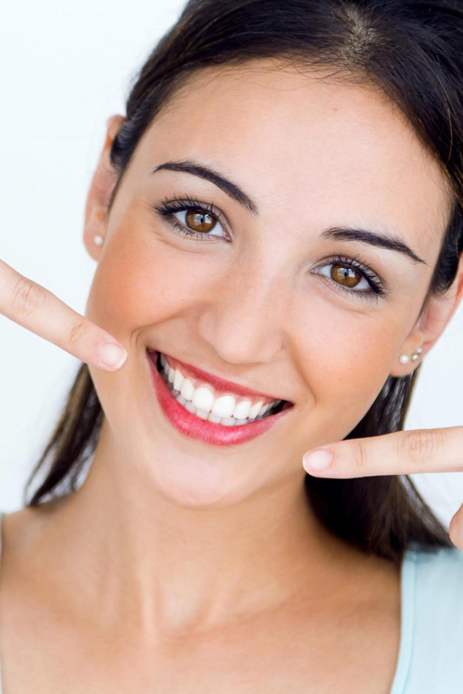 Mujer señalando su sonrisa
