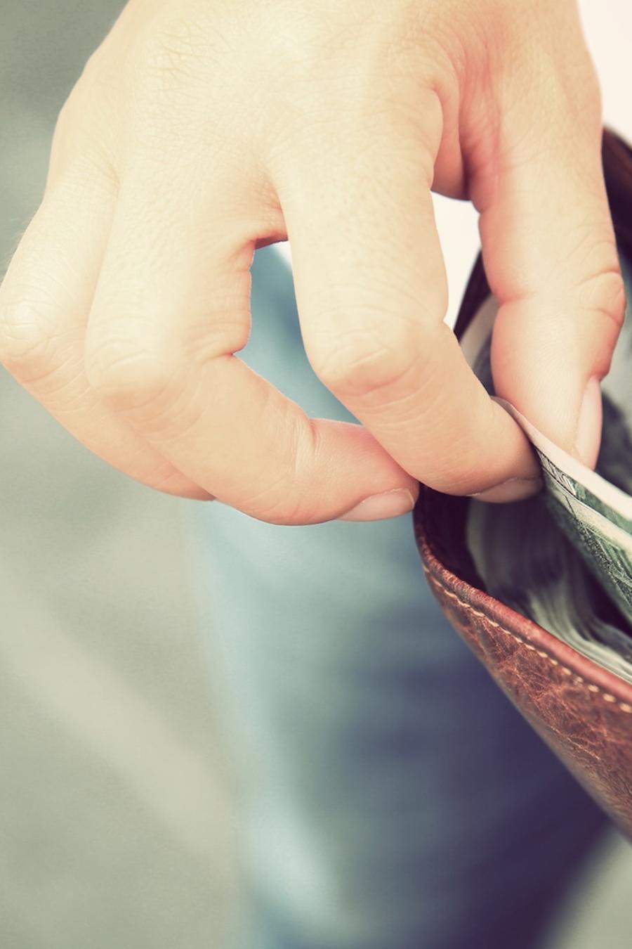 Persona tomando dinero de su billetera