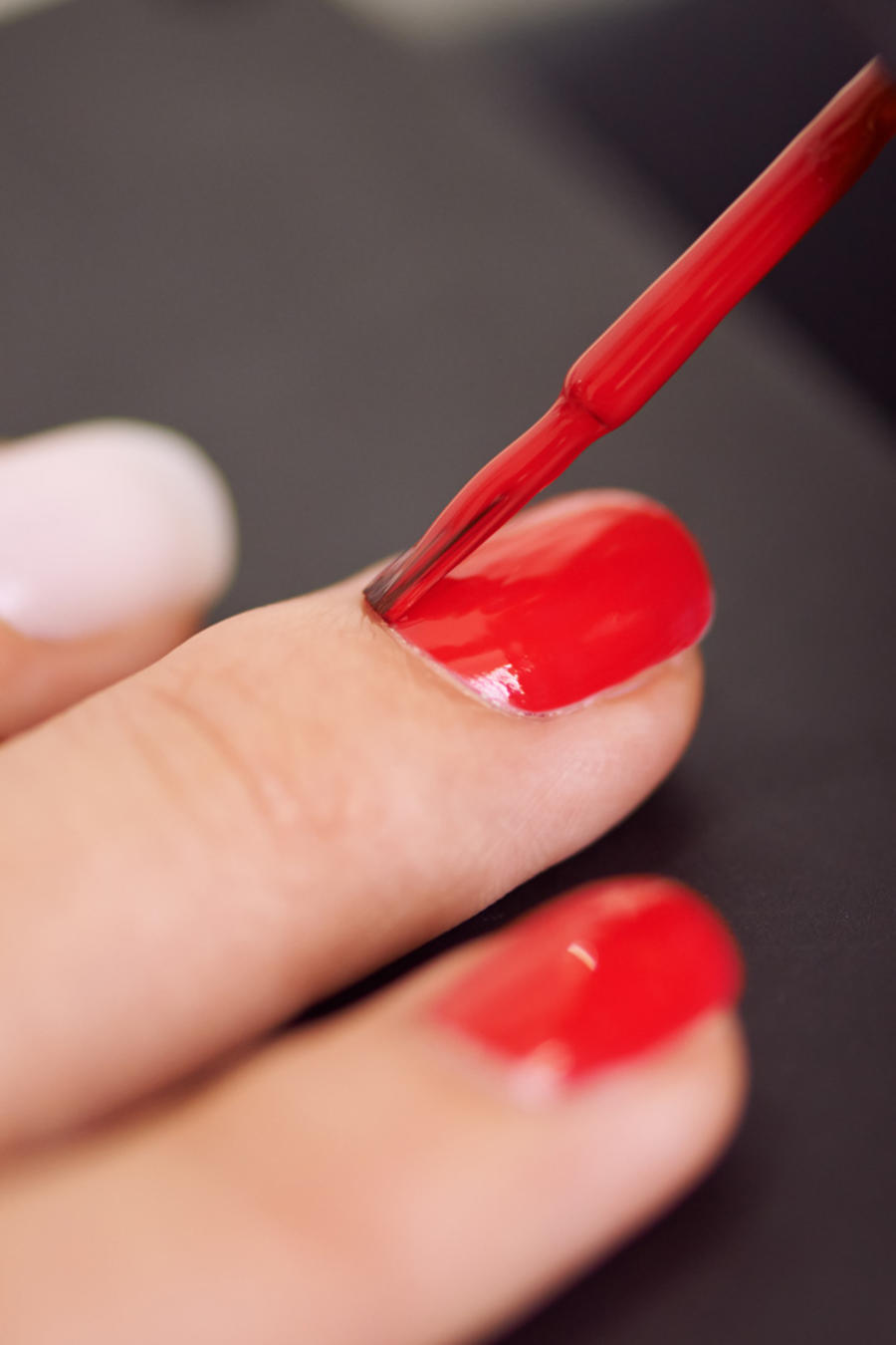 Mujer pintando sus uñas de color rojo
