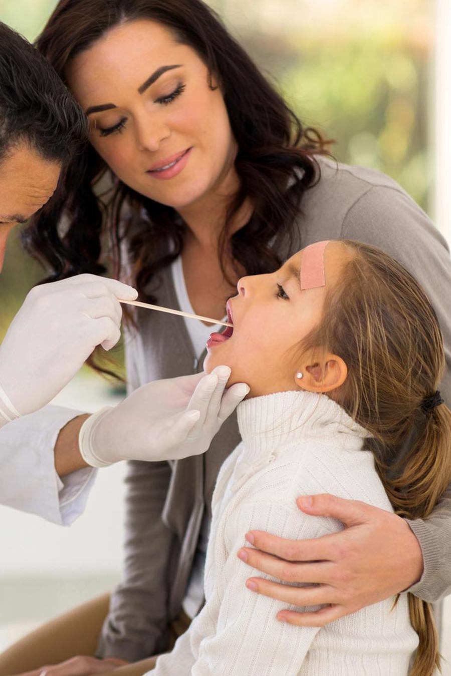 Doctor revisanto la garganta de una niña