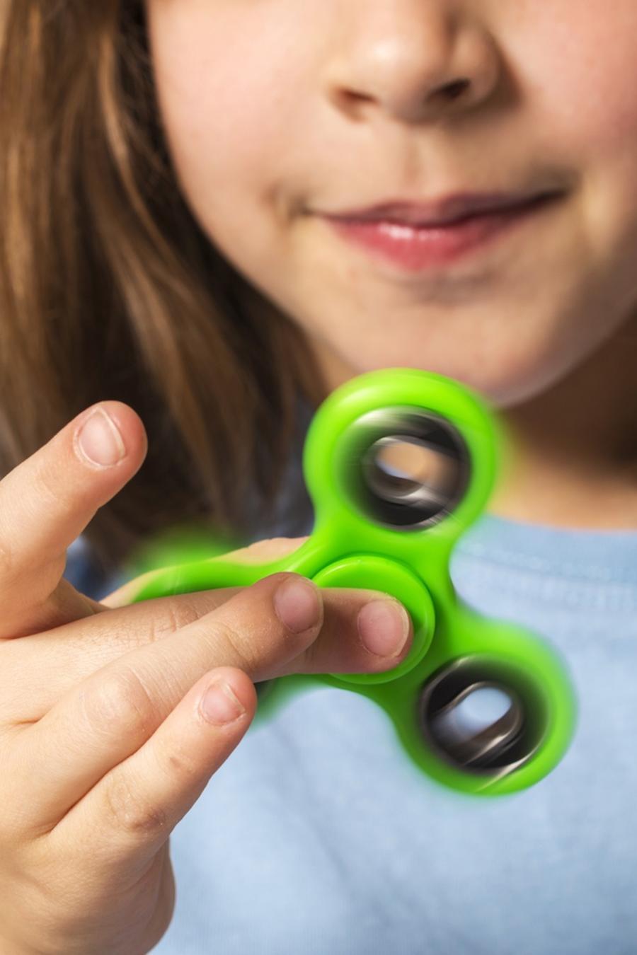 Niña pequeña usando fidget spinner