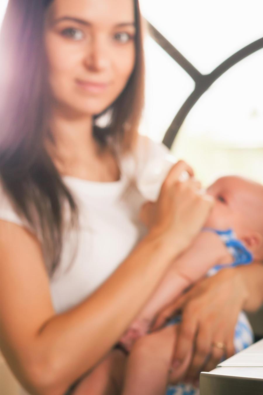 Mujer dando a un bebé el biberón, junto a un extractor de leche
