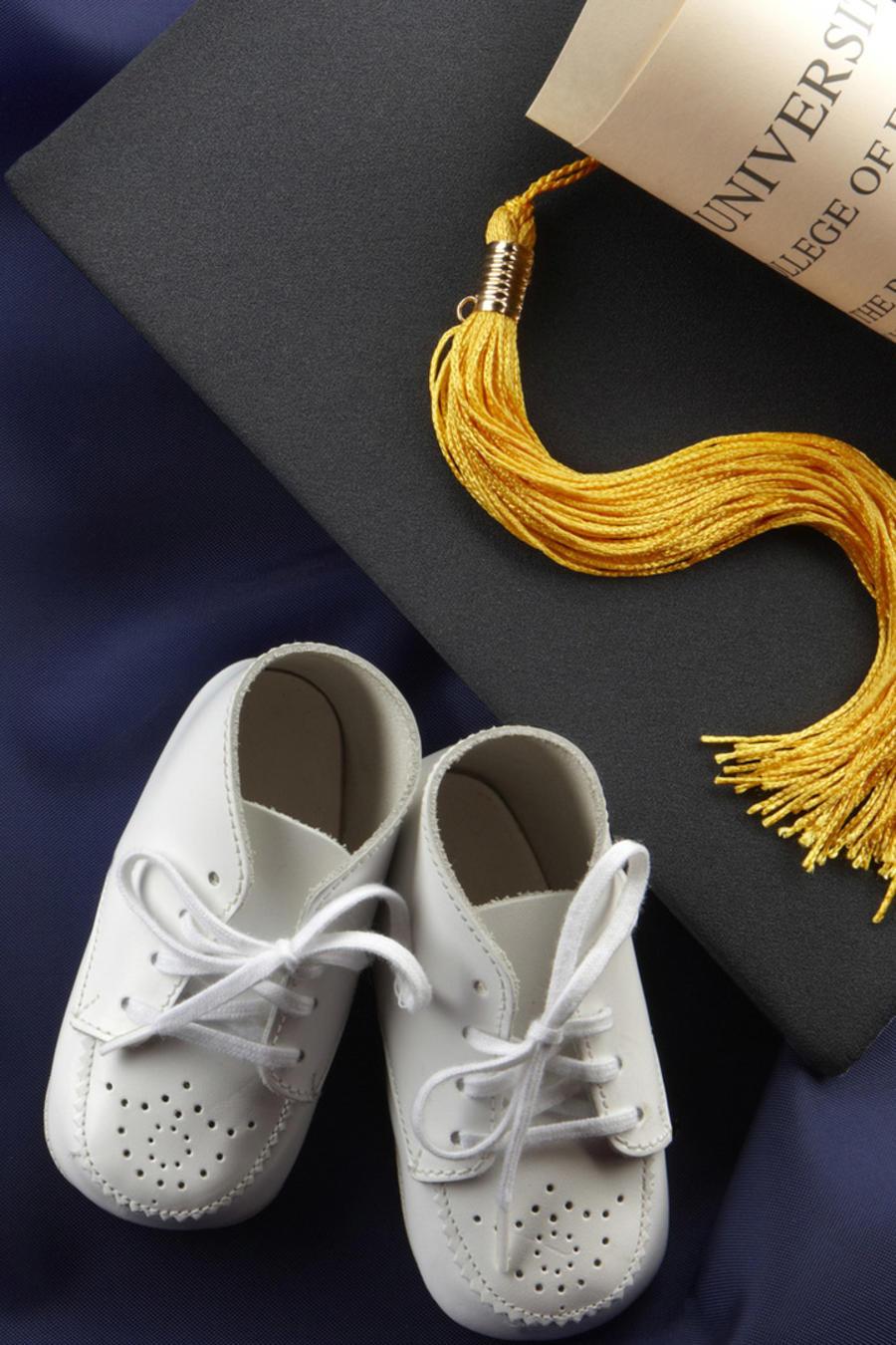 Zapatitos de bebé junto a birrete y título de graduación