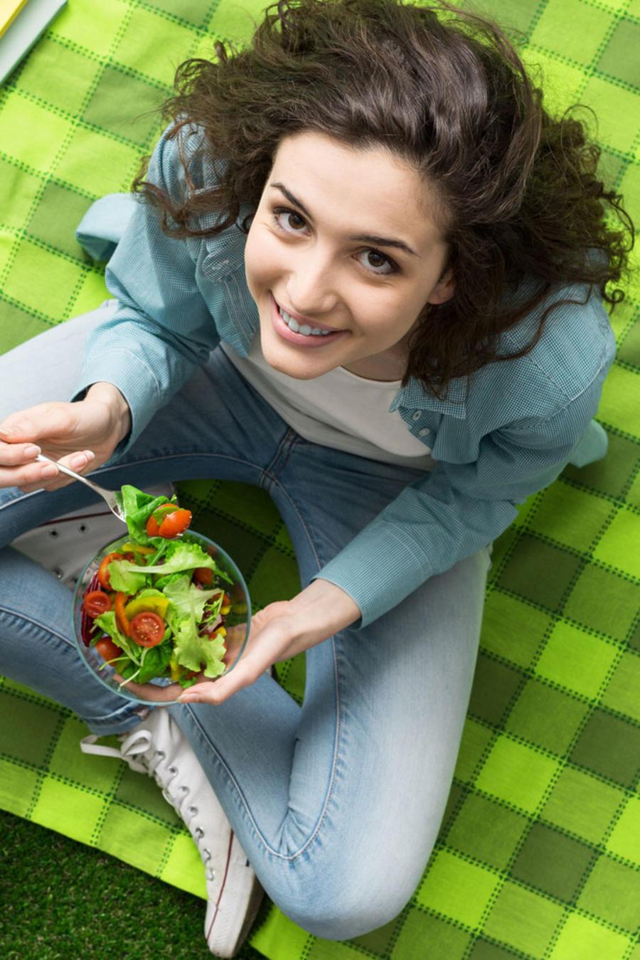 Mujer joven comiendo ensalada