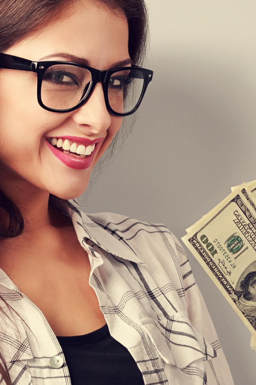 Mujer con gafas sonriendo, con billetes de dólar