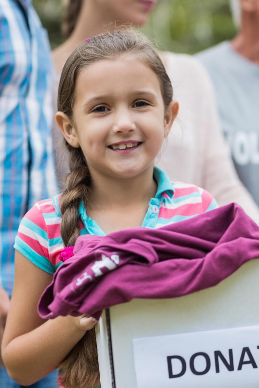 Niña con caja de donaciones participando de un voluntariado