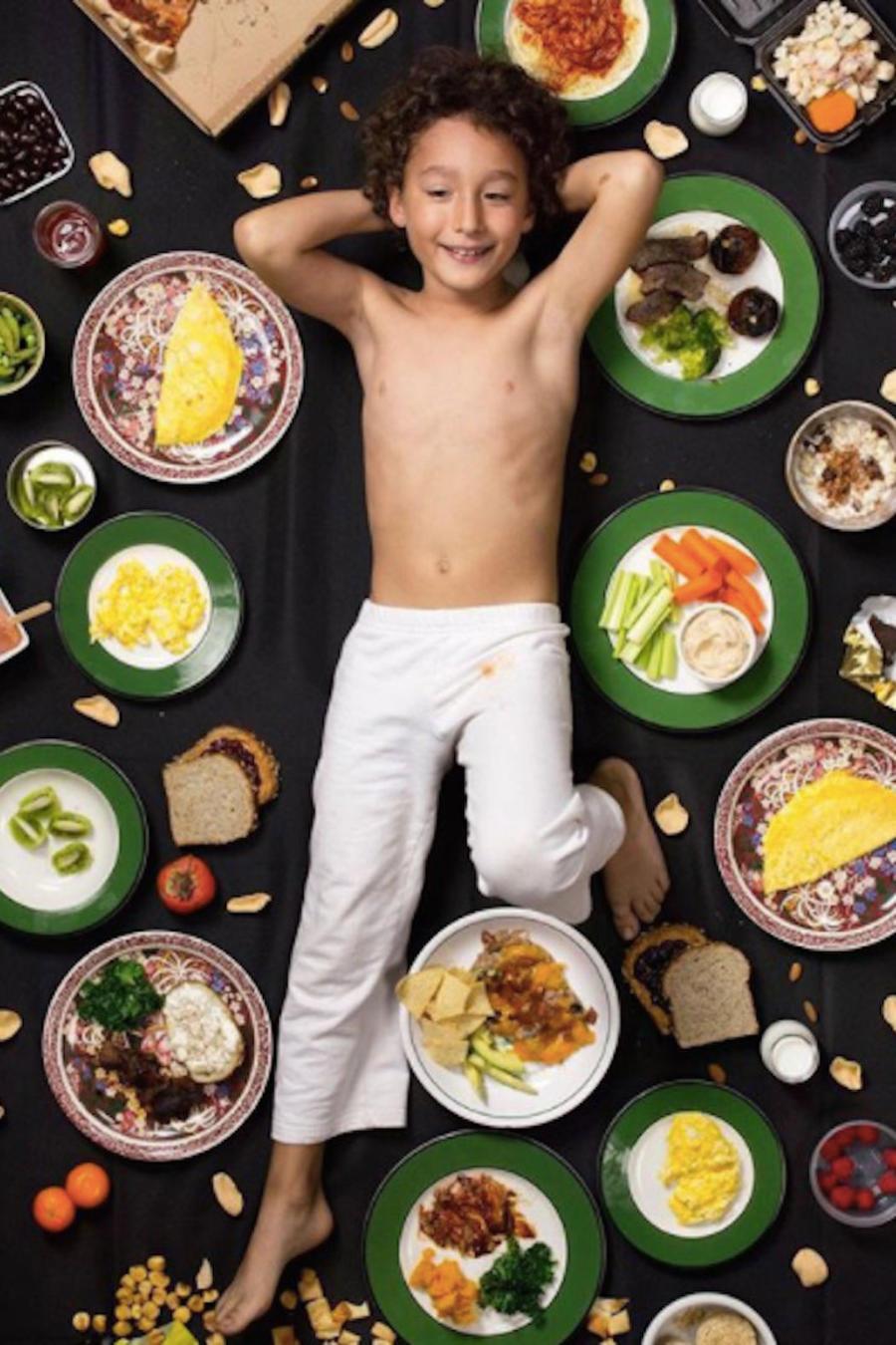 Niño acostado con comida alrededor