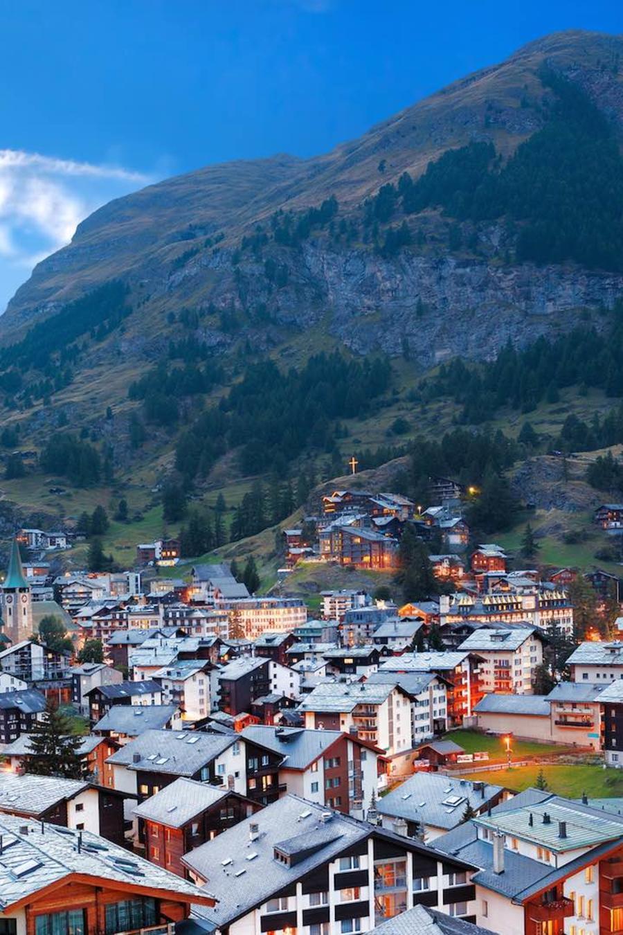 Bandera suiza y pueblo en las montañas