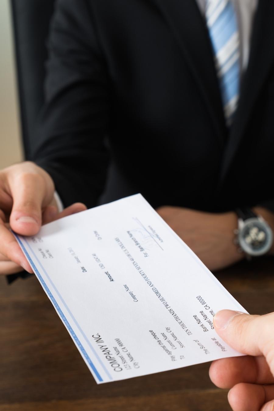 Jefe entregando cheque a empleado