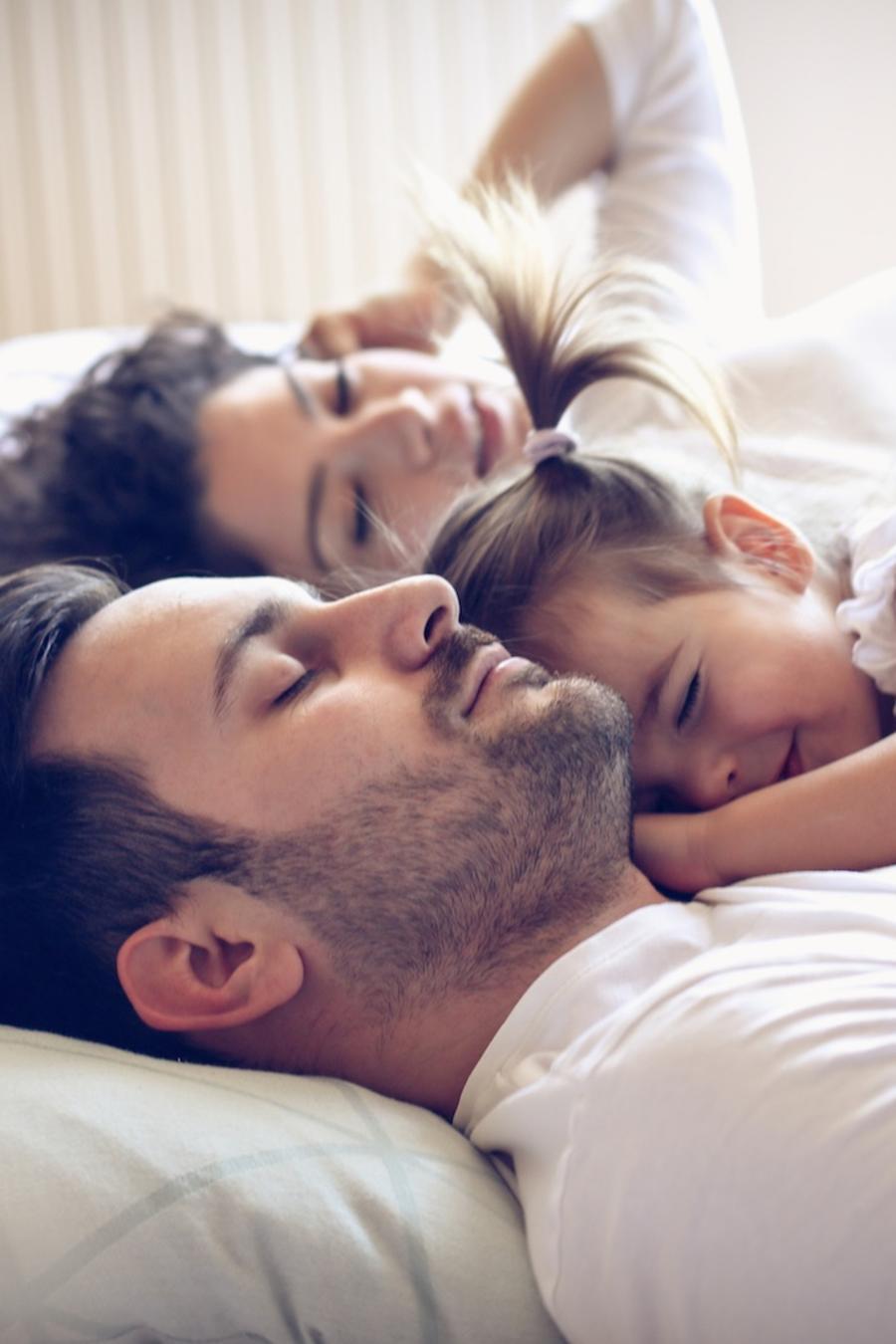 Madre y padre durmiendo con hija en la cama