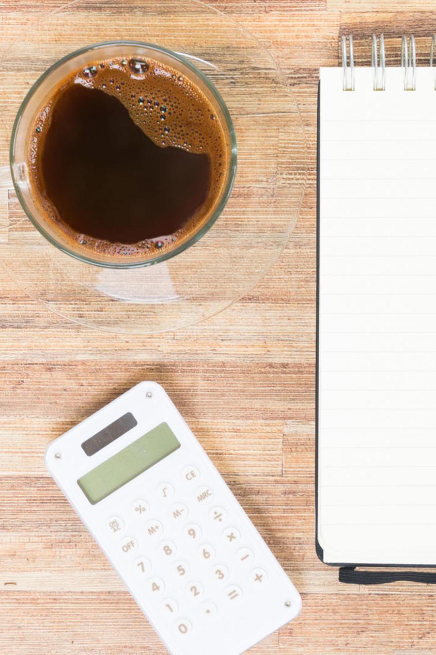 Cuaderno, calculadora y taza de café