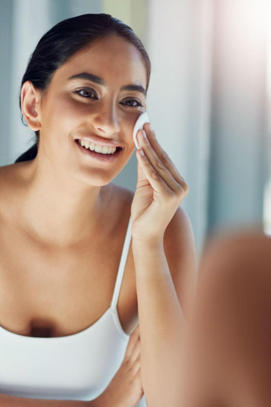 Mujer joven aplicándose crema frente al espejo