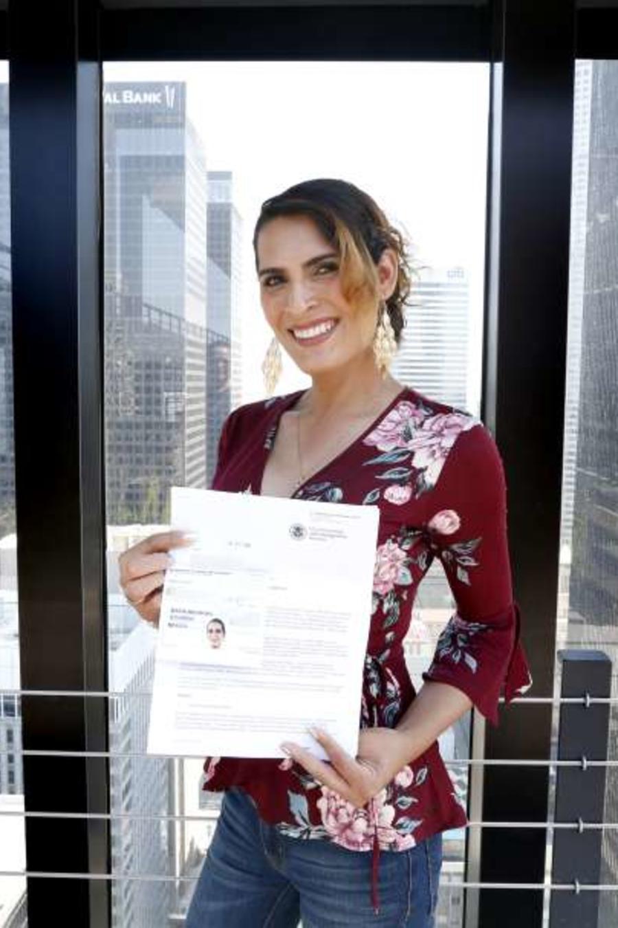 La inmigrante transgénero Victoria Murillo muestra el permiso migratorio tras recibir el asilo.