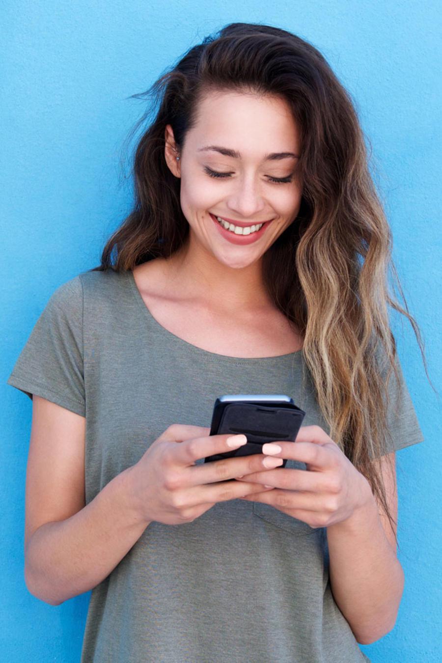 Chica sonriente con teléfono móvil