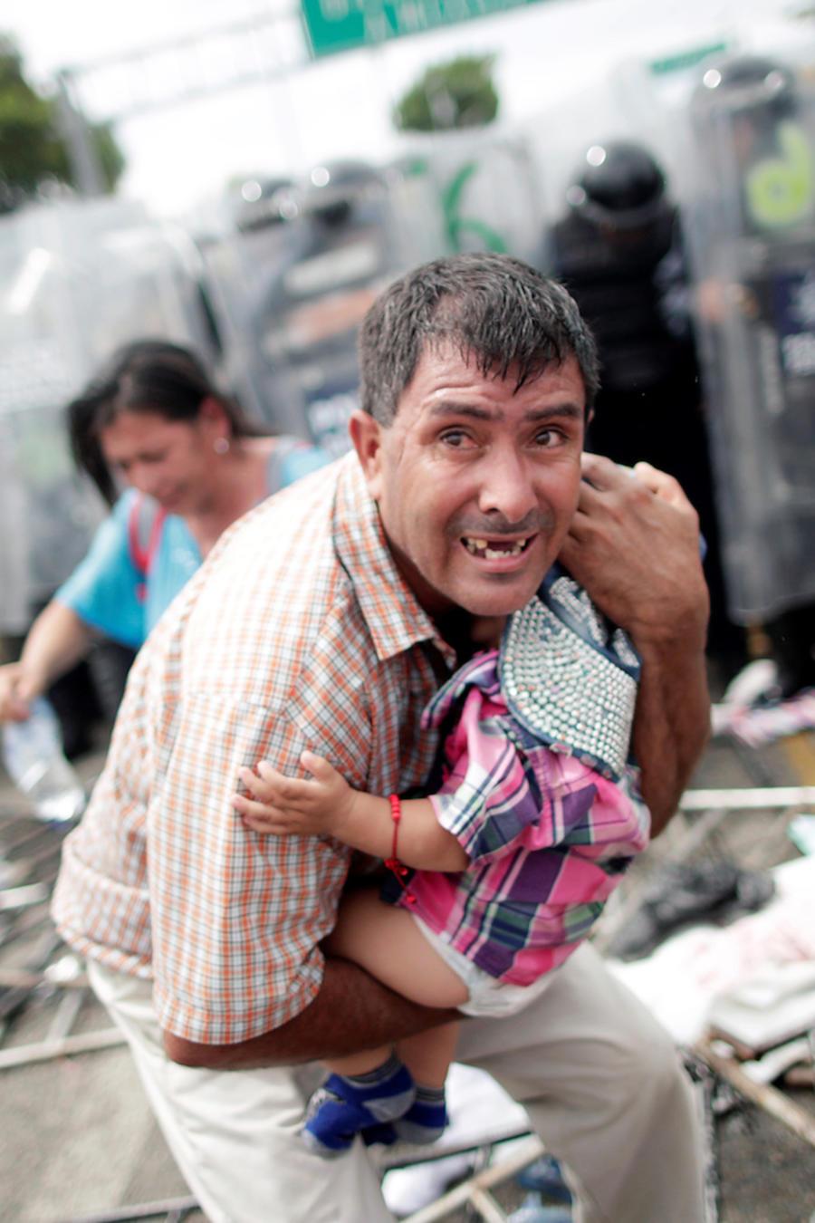 Un padre progege a su hijo mientras intenta cruzar a la carrera la frontera mexicana este viernes.