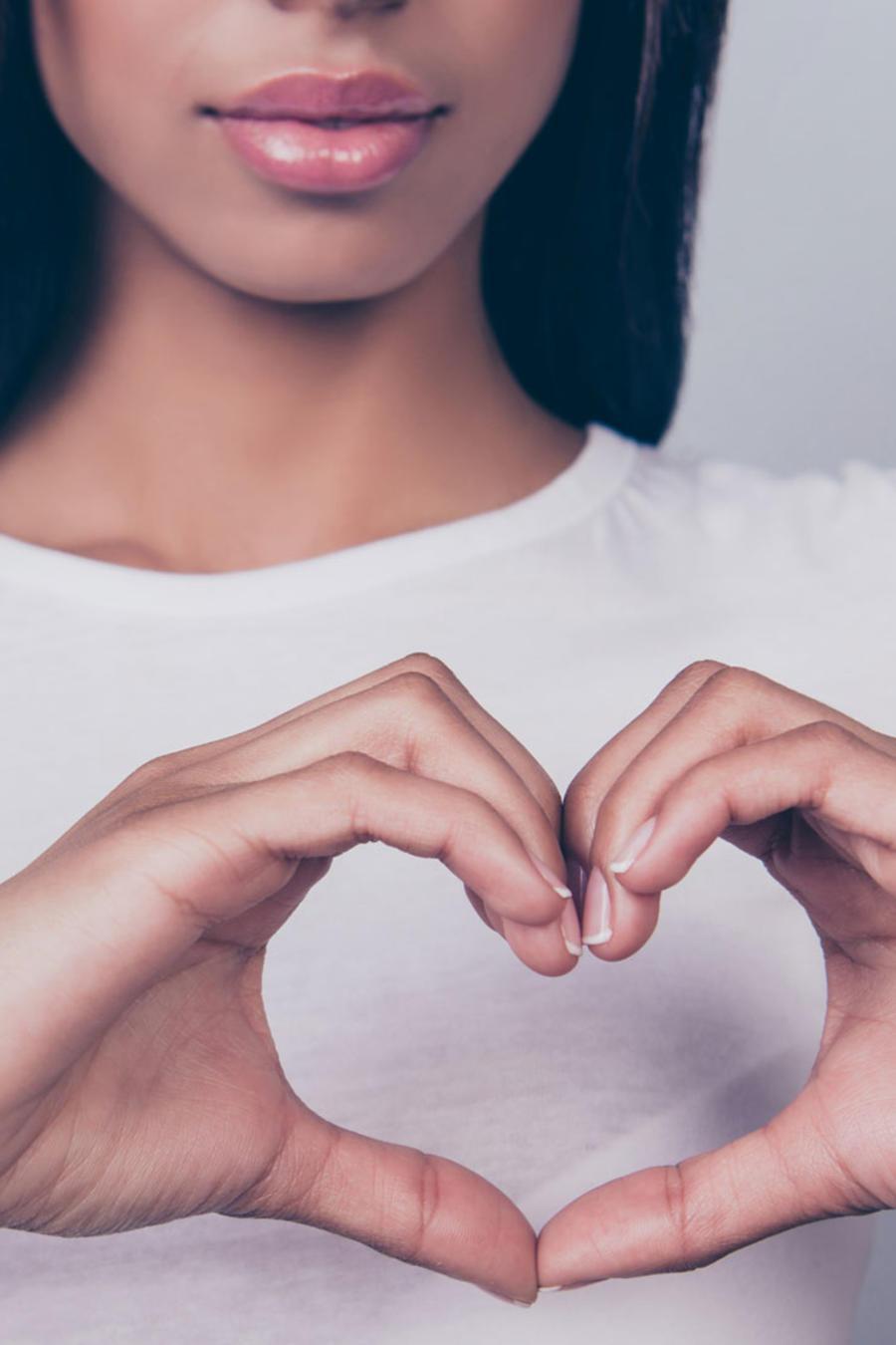 Mujer joven formando un corazón con las manos