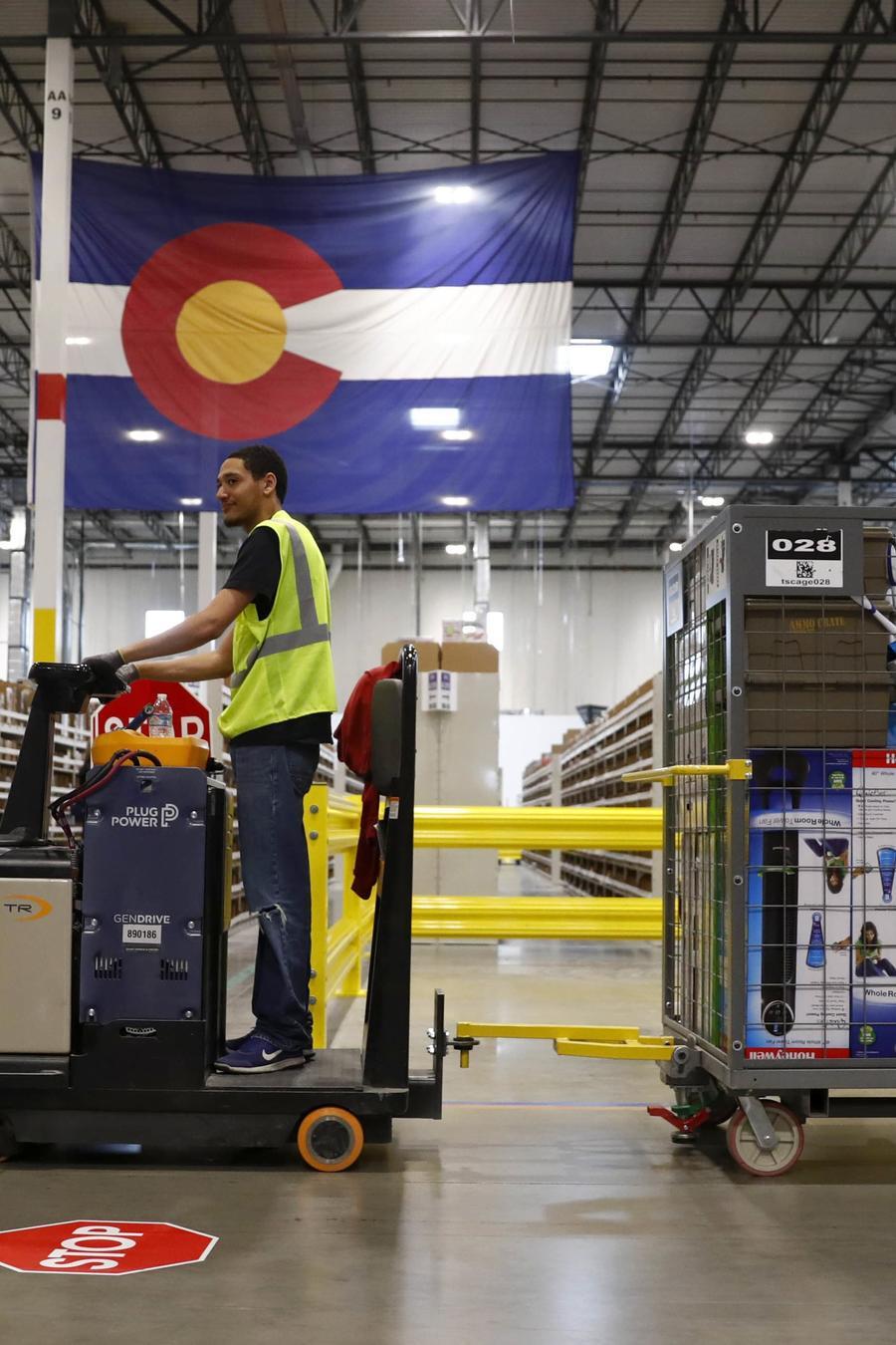 un trabajador de Amazon que conduce un montacargas en una bodega en Colorado