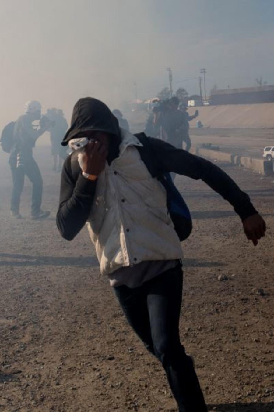 Migrantes huyen de los gases lacrimógenos lanzados por agentes de Estados Unidos en la frontera el domingo 25 de noviembre de 2018.