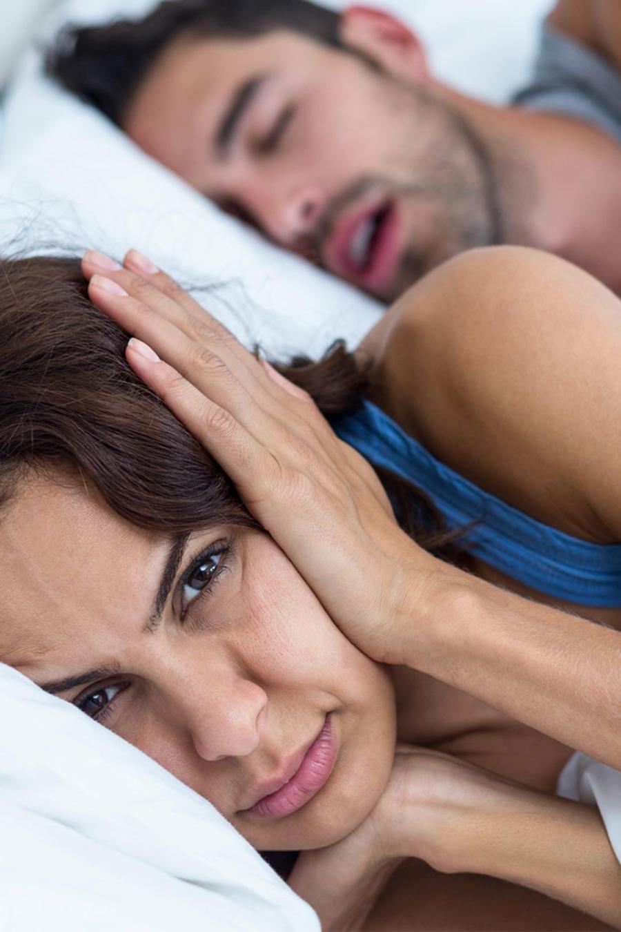 Mujer tapándose los oídos por el ronquido de su pareja
