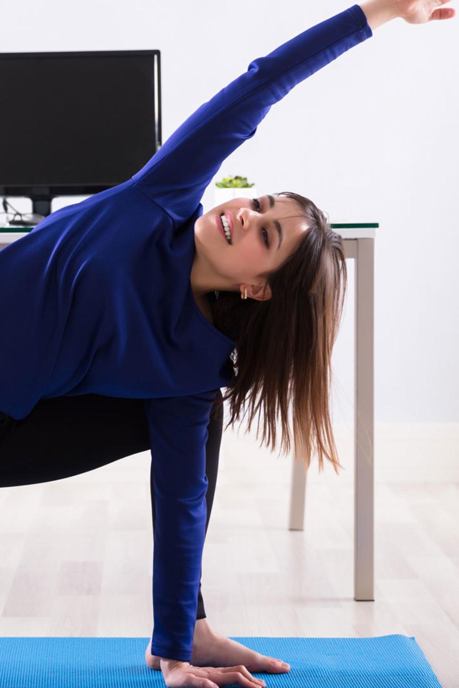 Mujer haciendo yoga en la oficina