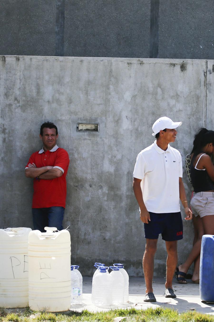 En esta fotografía de archivo del 12 de marzo de 2019, personas en Venezuela hacen una fila para llenar bidones de agua durante un apagón eléctrico
