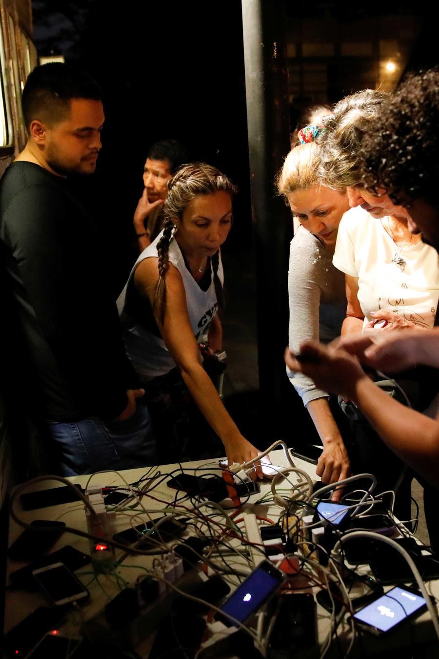 Venezolanos en Caracas se reúnen en una plaza pública a cargar sus celulares con un generador el 26 de marzo de 2019