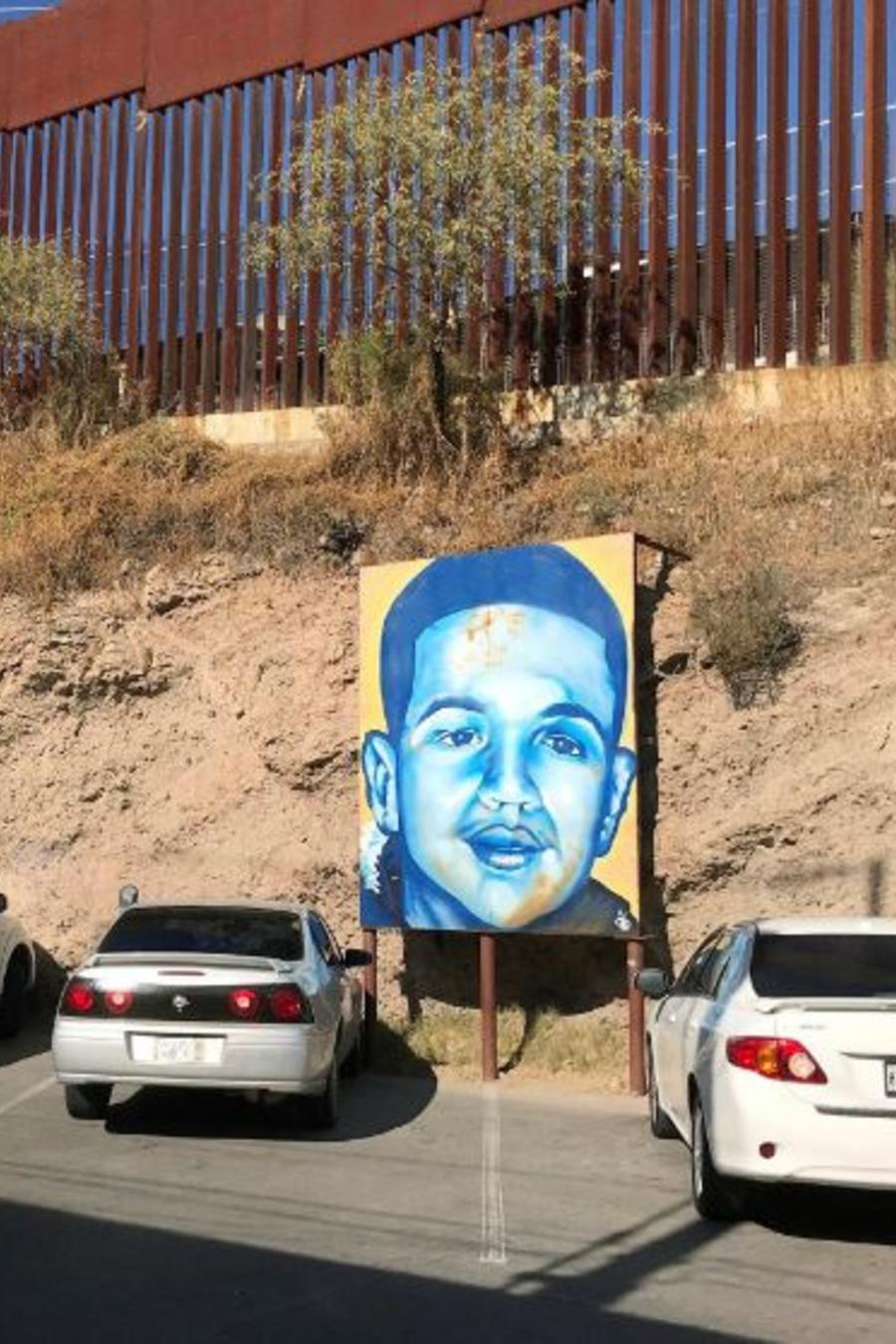 En esta fotografía de archivo del 4 de diciembre de 2017, un retrato del joven mexicano José Antonio Elena Rodríguez, que fue muerto a balazos en Nogales, Sonora, México, yace a la vista en la calle de Nogales en la que fue asesinado, junto a la frontera