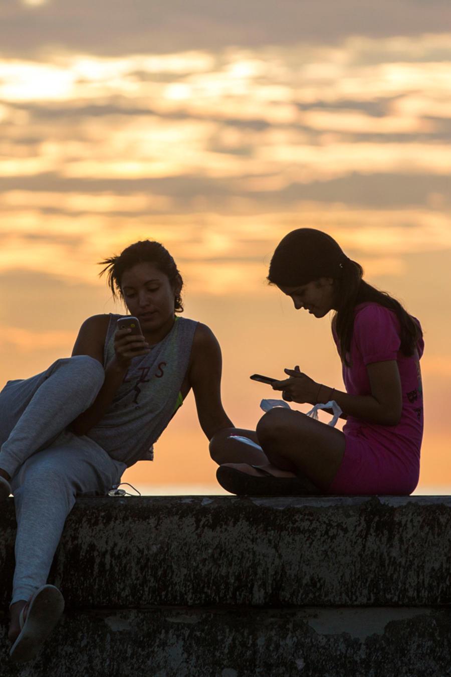 Dos jovencitas en La Habana con sus celulares en una imagen de archivo
