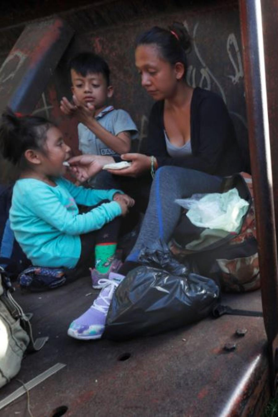Una madre migrante y sus hijos viajan en un tren de carga hacia el norte, en Palenque, estado de Chiapas, México, el lunes 24 de junio de 2019.