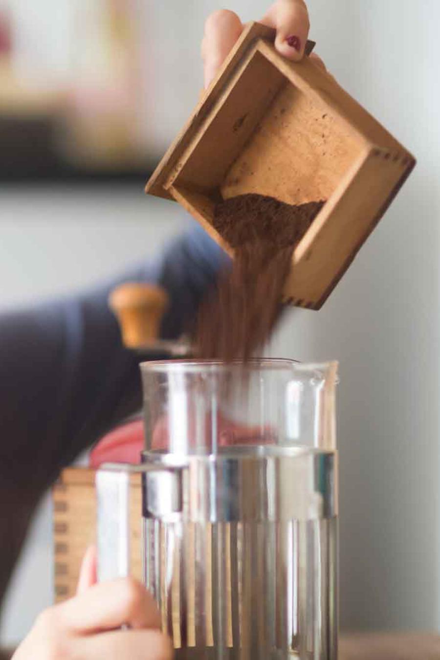 Mujer vertiendo borra de café en un recipiente