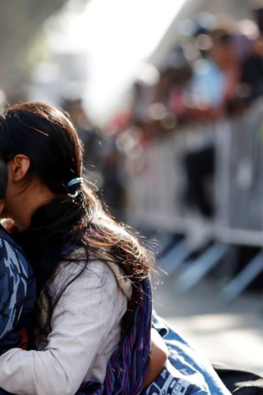 Una mujer y su hijo esperan para solicitar asilo en Estados Unidos a lo largo de la frontera, el martes 16 de julio de 2019, en Tijuana, México.