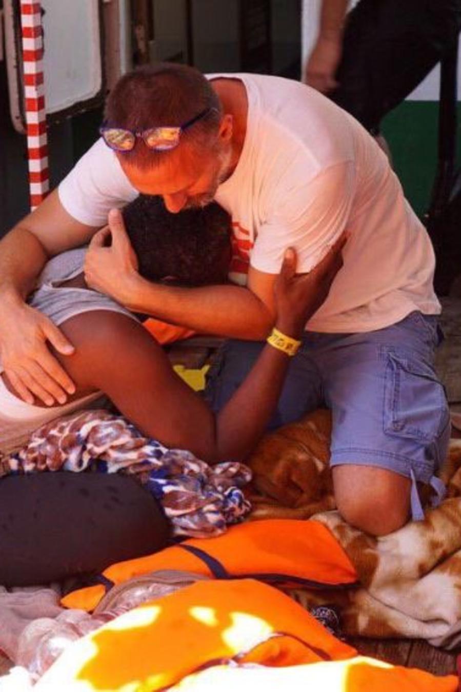 Un inmigrante es consolado por un tripulante del barco español humanitario Open Arms frente a la costa de la isla siciliana de Lampedusa, en el sur de Italia, el domingo 18 de agosto