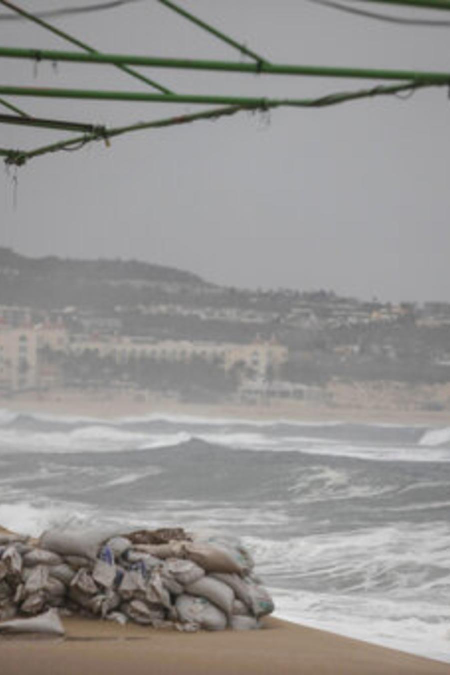 Un turista toma fotos del océano en la playa El Médano antes de la llegada esperada del huracán Lorena, en Los Cabos