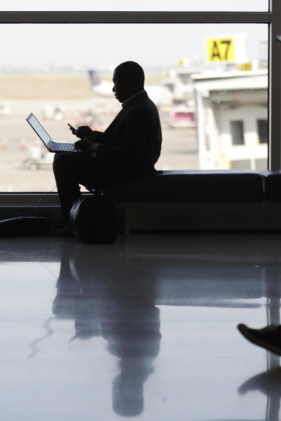Viajeros en sus dispositivos electrónicos en el Aeropuerto Internacional de Indianneapolis, Indiana