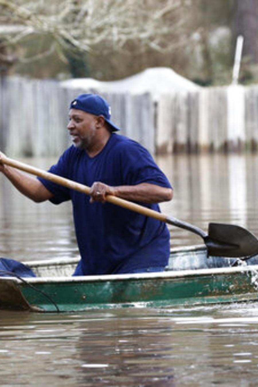 Dos hombres reman por las calles inundadas por el río Pearl en Jackson, Mississippi.