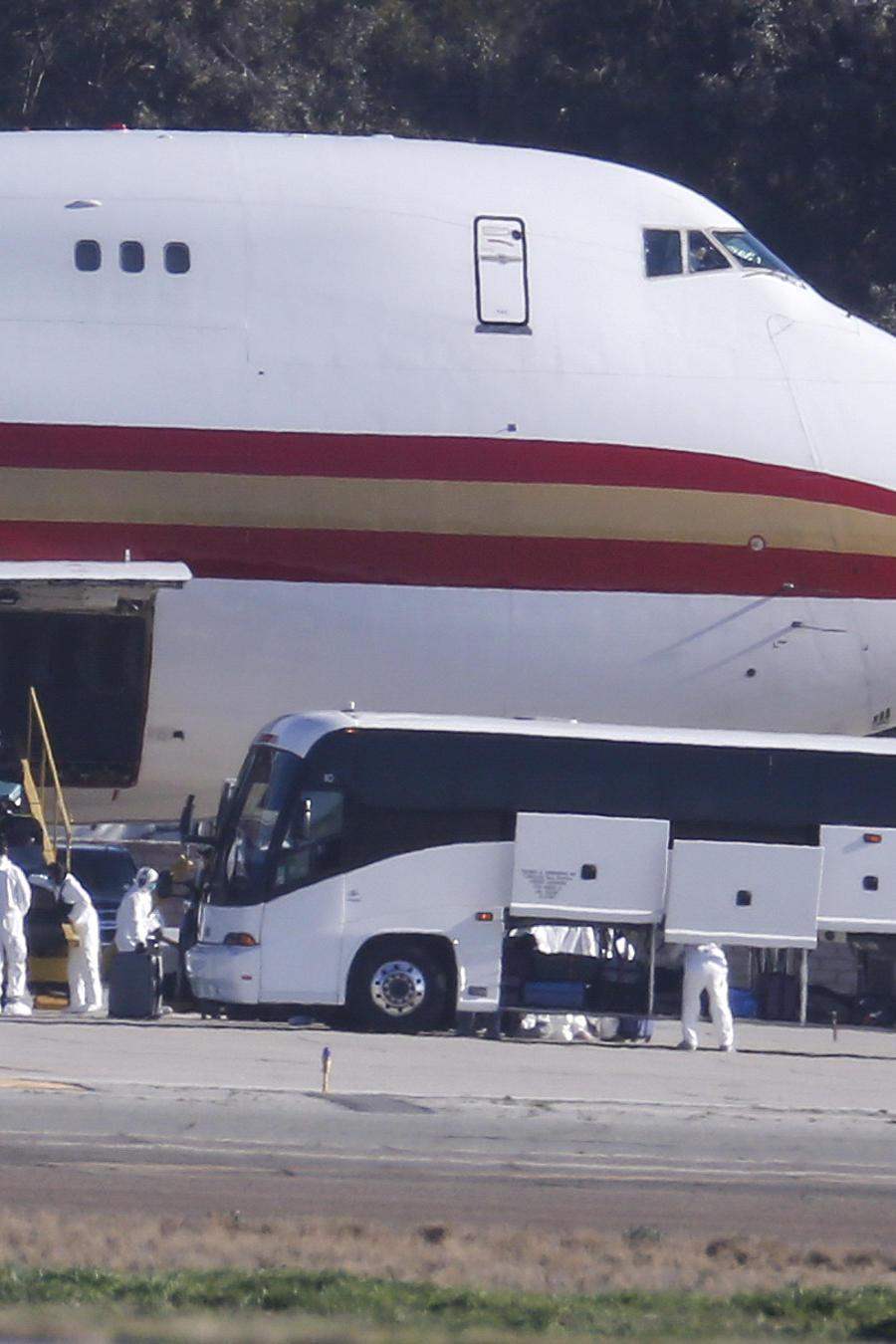 Personal con trajes protectores en California descarga el equipaje deevacuados de China por el coronavirus