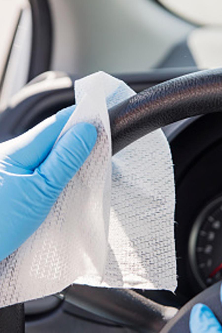 Una persona desinfecta su auto en una imagen creativa.