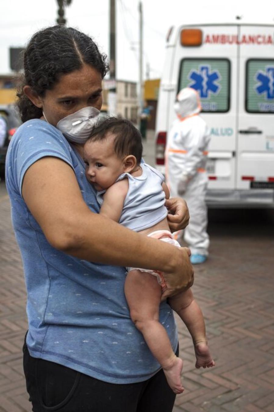 Una mujer venezolana con su bebé de 3 meses espera afuera de un albergue para personas sin techo en Perú.