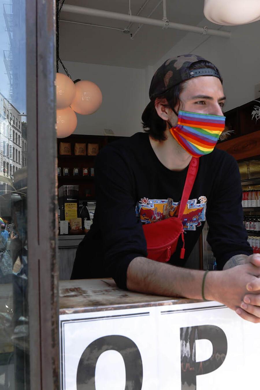 Desde una cafetería, una persona observa una marcha en Manhattan usando una mascarilla con los colores de la bandera LGBTQ.