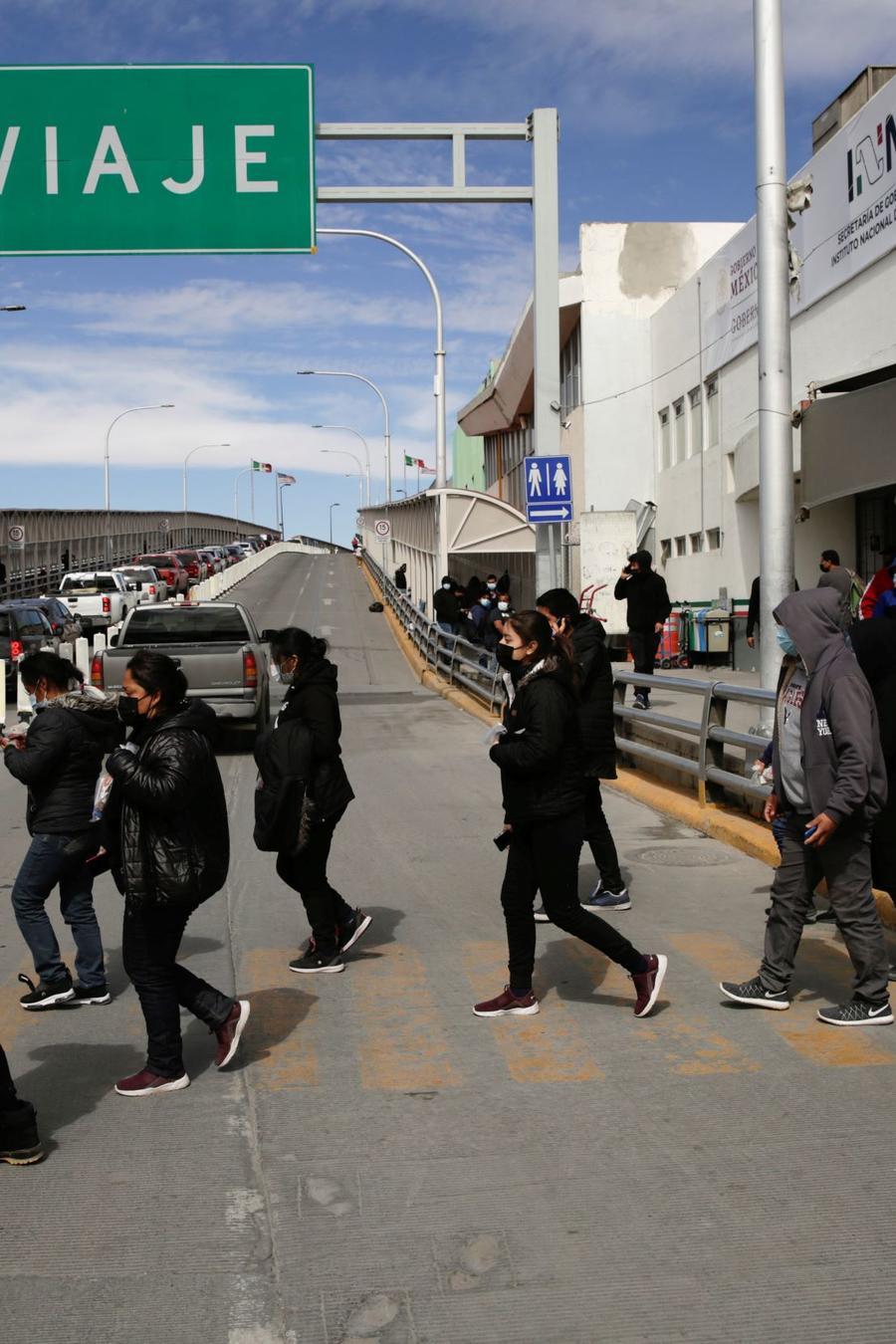 Inmigrantes deportados por la administración Biden cruzan el puente fronterizo Paso del Norte hacia Ciudad Juárez, el 25 de febrero del 2021.