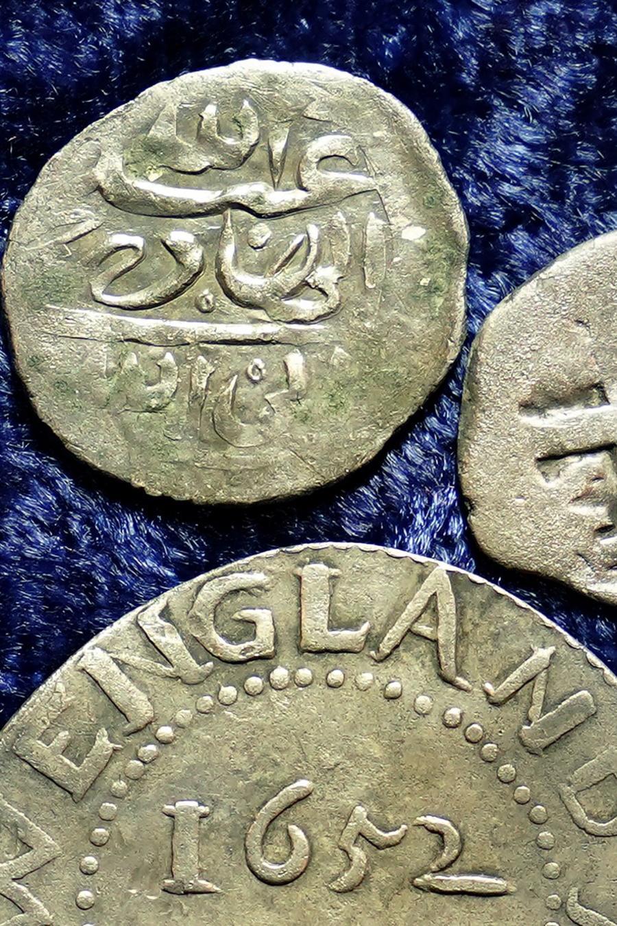 Una moneda árabe de plata del siglo XVII se aprecia en la parte superior junto a otra moneda acuñada en 1652 por la Colonia de la bahía de Massachusetts, abajo, y una moneda española de medio real de 1727, a la derecha.