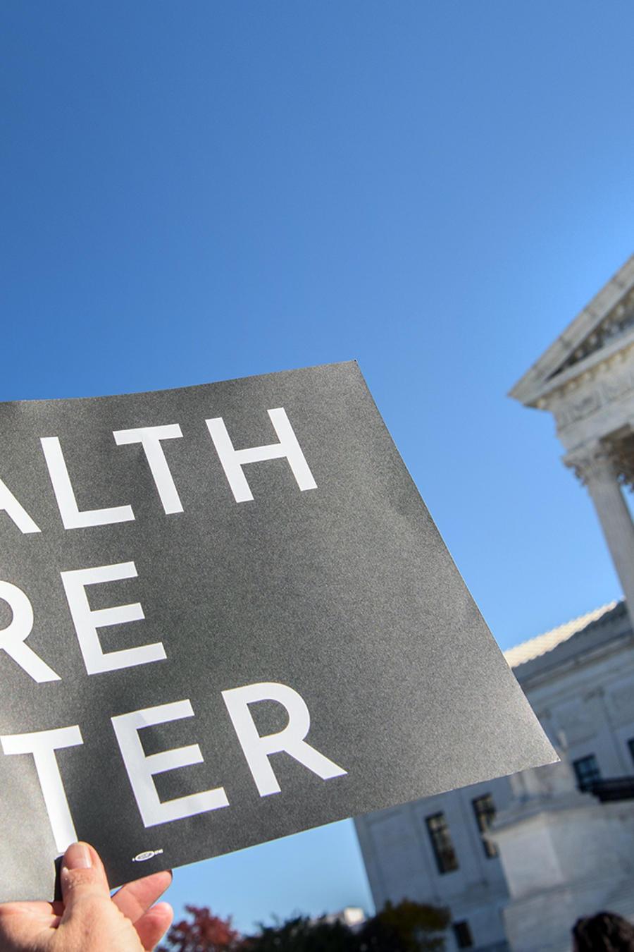 Un manifestante sostiene un cartel frente a la Corte Suprema en Washington, DC, el 10 de noviembre de 2020, cuando el Tribunal Superior abrió argumentos en el caso de larga data sobre la constitucionalidad de la Ley del Cuidado de Salud a Bajo Precio de 2