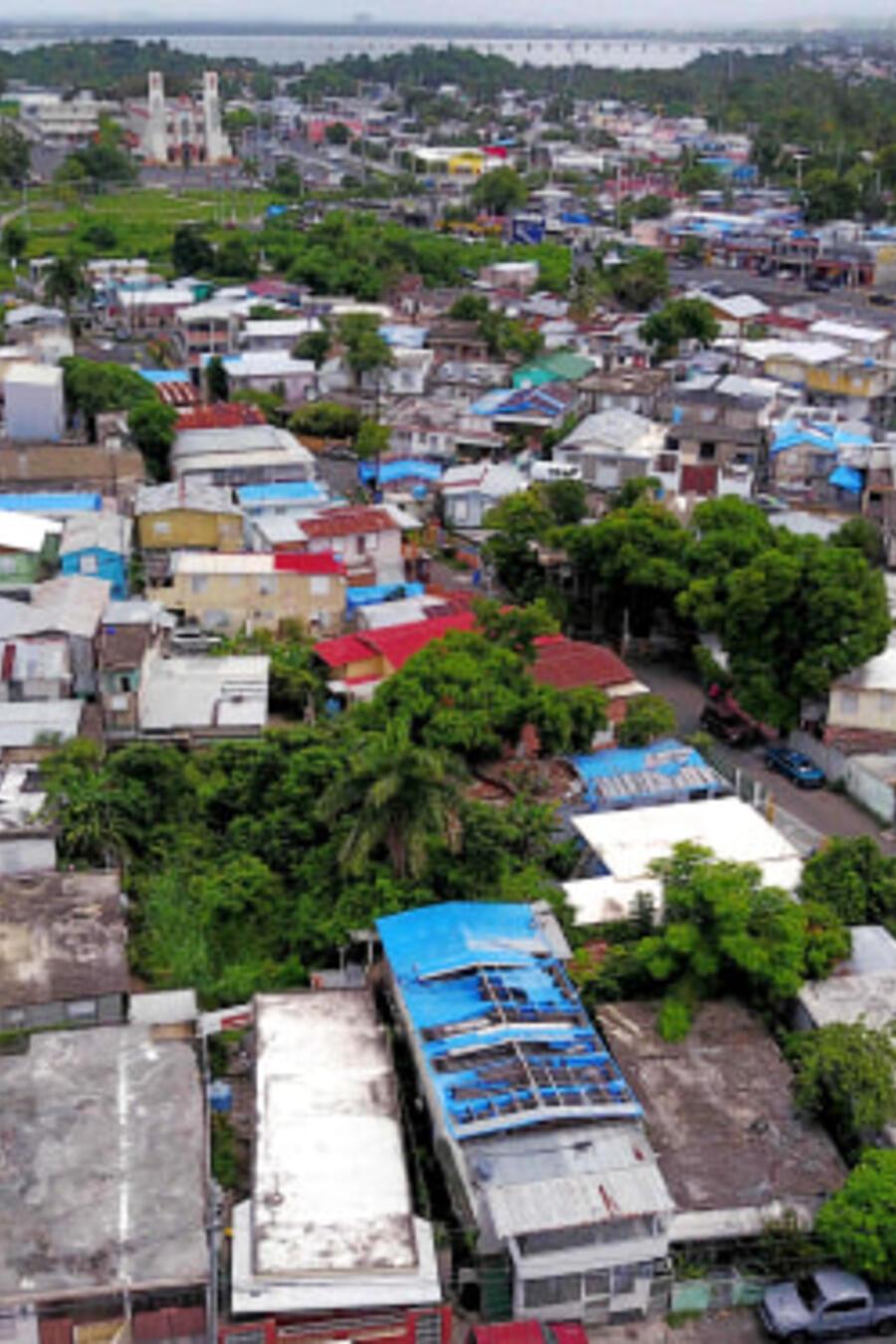 Lonas azules repartidas por FEMA cubren varios techos de viviendas dañadas en Puerto Rico dos años después del huracán María.