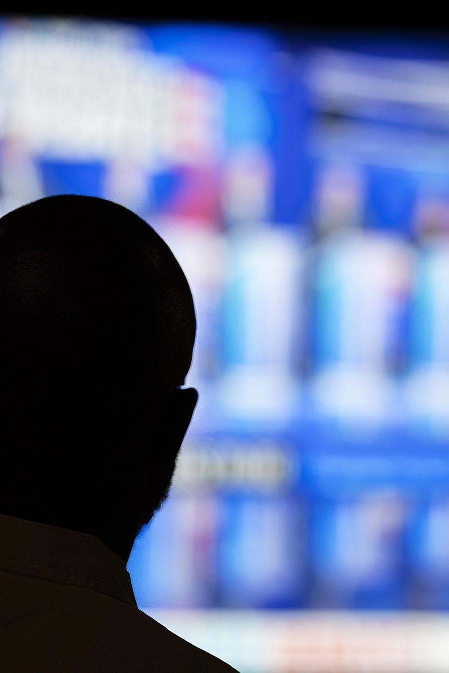 Un hombre observa la transmisión del debate presidencial demócrata realizado el 27 de junio de 2019