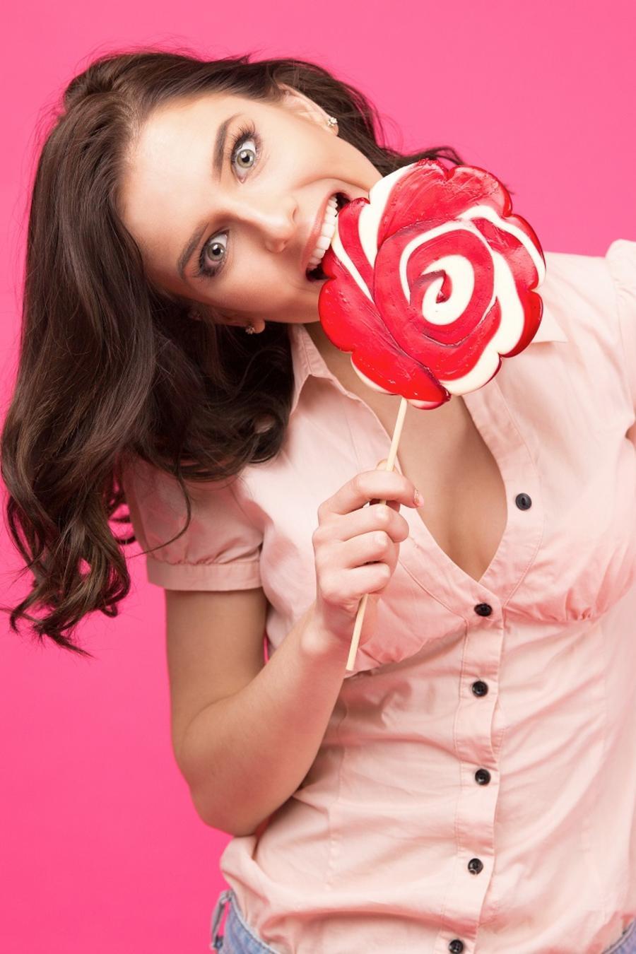 chica mordiendo una lollipop blanca con rojo