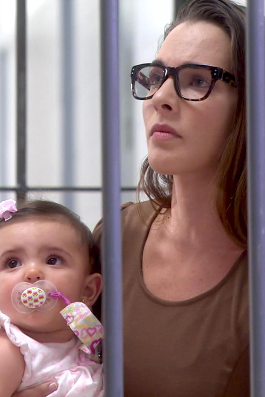 Kendra Santacruz cargando a una bebé en la cárcel en Bajo El Mismo Cielo